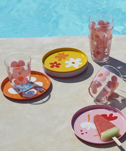 Színes tányérok és poharak, virágos mintával egy medence mellett.