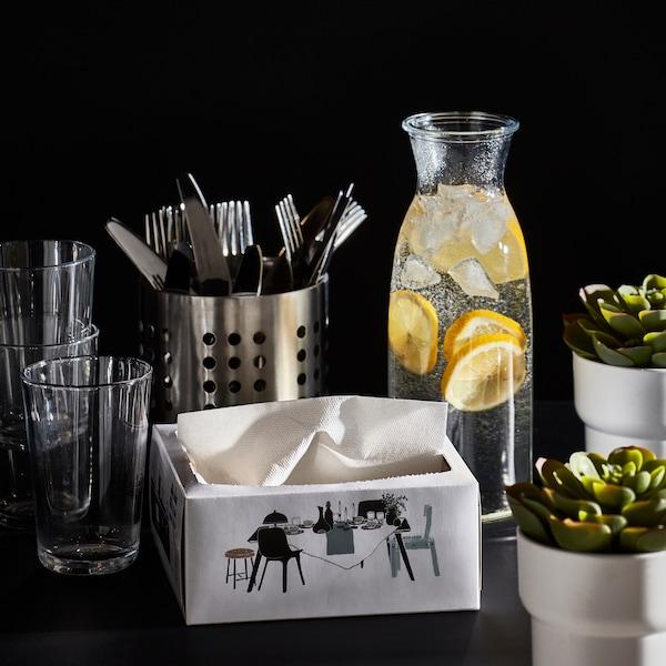 Szklanki, sztućce, karafka z wodą i plastrami cytryny, białe serwetki papierowe i dwie małe roślinki.