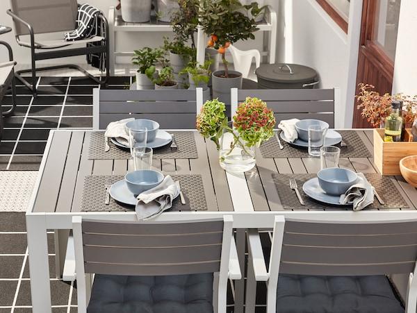 Szürke kültéri asztal, fekete tányéralátétekkel, kék/szürke étkészlettel, evőeszközökkel, vászonszalvétákkal, és virágokkal egy vázában.