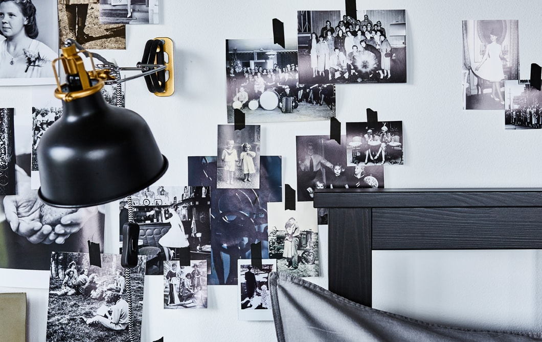Szukasz pomysłów do małej sypialni? Upiększ ramę łóżka kolażem zdjęć na ścianie. Oświetl ją lampą, taką jak czarny reflektor ścienny/z klamrą IKEA RANARP N. Światło można z łatwością skierować w dowolne miejsce, ponieważ klosz lampy jest regulowany.