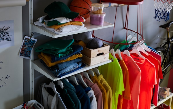 T-Shirts auf Kleiderbügeln am unteren Stahlgestell eines IKEA TRANARÖ Hockers/Beistelltisch innen/außen in Rot, der an der Wand befestigt wurde.