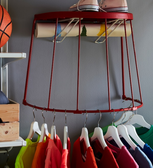 T-shirts on hangers, hung on the bottom steel frame of a red IKEA TRANARÖ stool attached to the wall.
