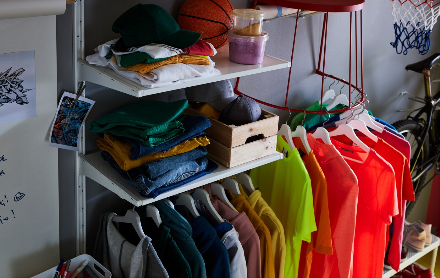 T-shirts on shelves and on hangers, hung on the bottom steel frame of a red IKEA TRANARÖ stool attached to the wall.