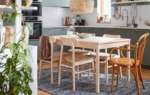 Table à dîner en bouleau et quatrechaises de la collection RÖNNINGE ainsi qu'une chaise IKEA des années60.