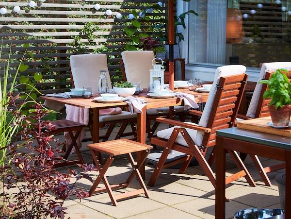 Table à manger avec rabats, 4 chaises à dossier réglable et 2 tabourets pliants en acacia. De la vaisselle blanche est disposée sur la table.