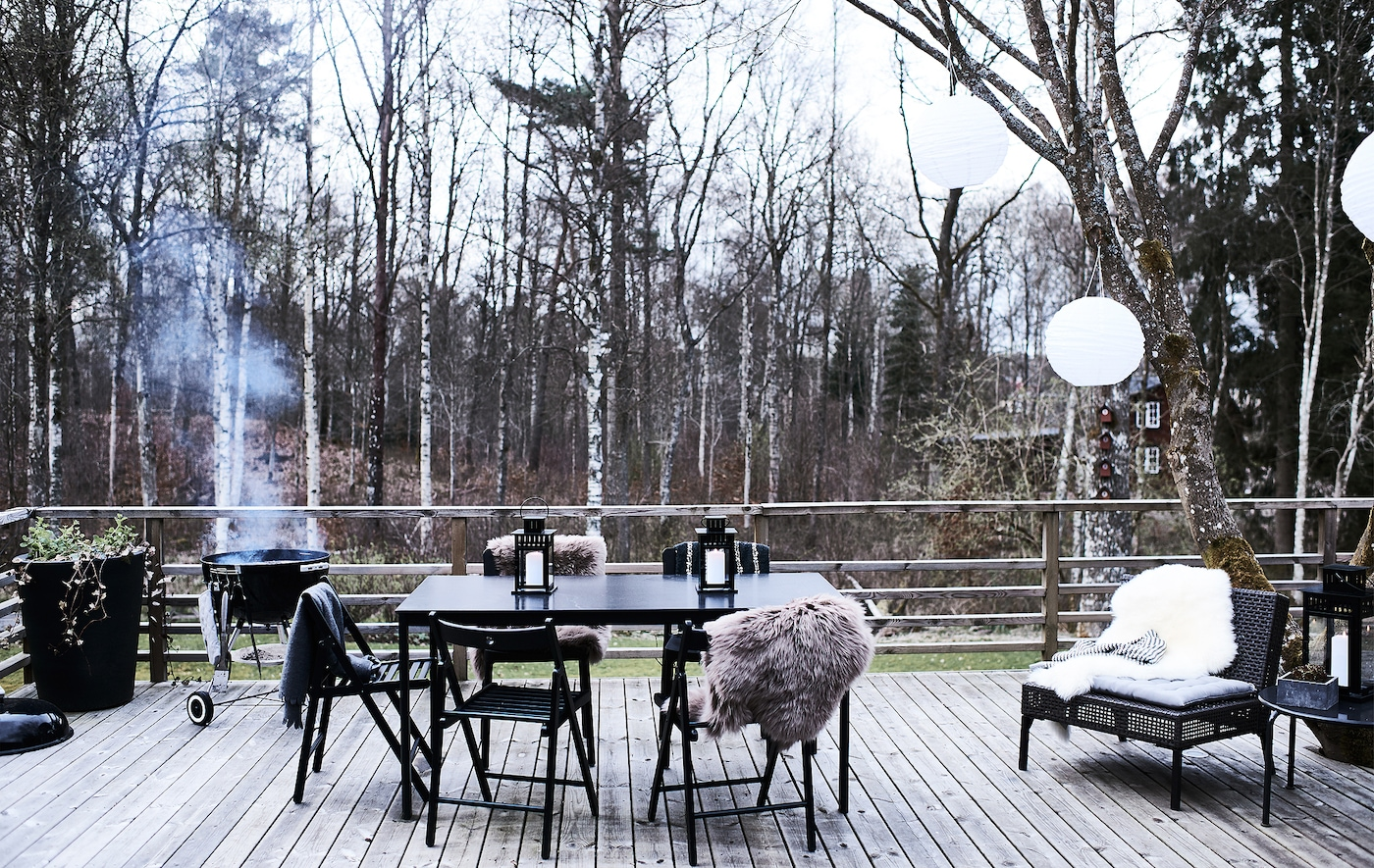 Table à manger et chaises sur une terrasse en bois avec barbecue allumé dans le fond