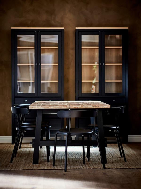 Table à manger SKOGSTA avec dessus en bois clair et pieds foncés, entourée de chaises YNGVAR anthracite. Armoires foncées près du mur.
