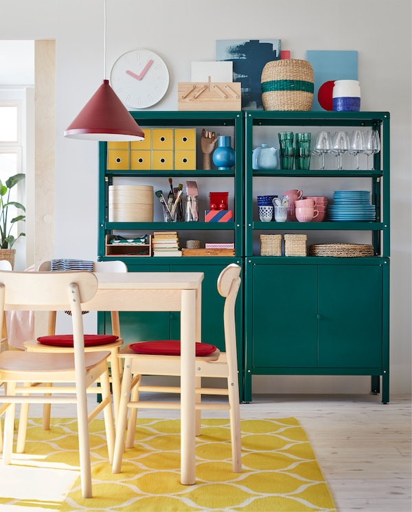 Table and chairs in birch, red chair pads, a yellow rug, a dark red pendant lamp and two green shelving units with cabinets.