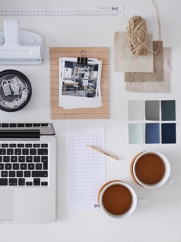 Table avec deux tasses de thé, un ordinateur, un bloc-notes et des cartons dans différentes couleurs