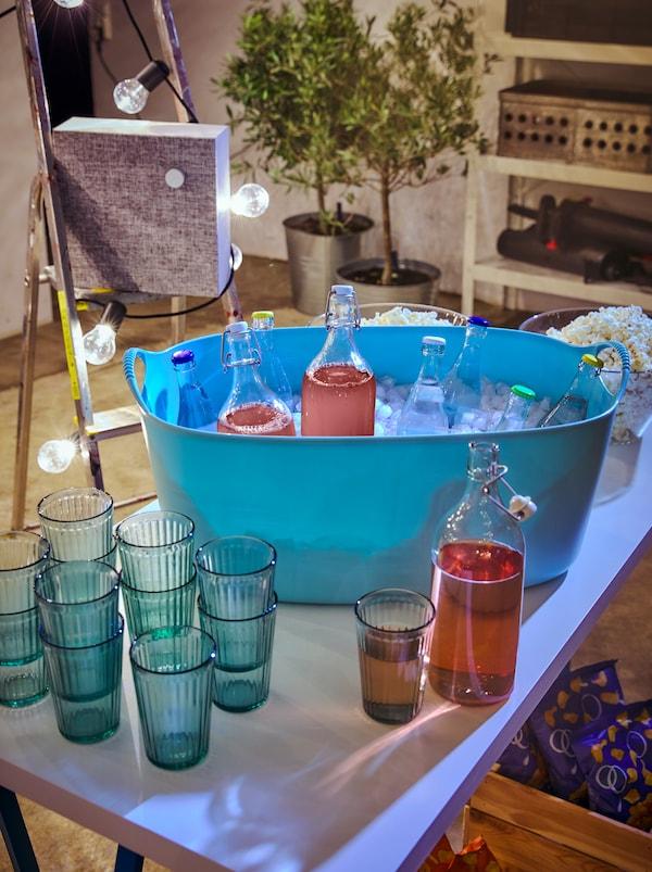Table avec verres KALLNA empilés à côté d'un panier à linge TISKEN rempli de glace et de boissons dans des gobelets fermés, y compris des bouteilles en verre KORKEN.