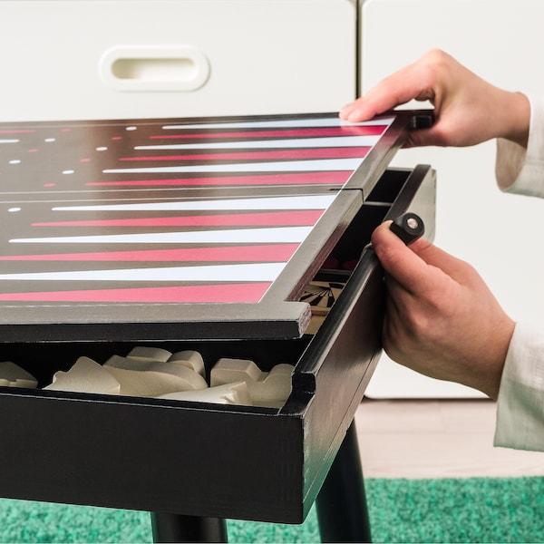 Table basse avec un plateau de backgammon peint sur le dessus. Des mains soulèvent le couvercle de la table, révélant plusieurs jeux rangés à l'intérieur.