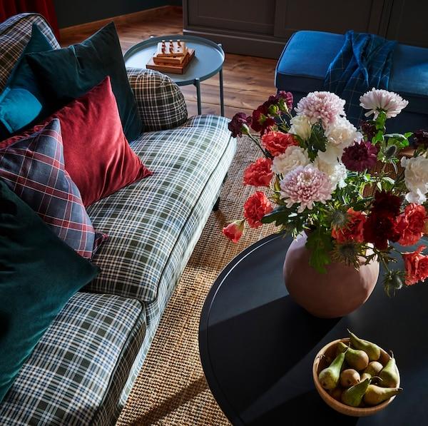 Table basse KRAGSTA en bois noire, vase fait à la main INDUSTRIELL en terre cuite brune et table-plateau GLADOM en métal bleu vif.