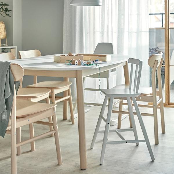 Table, chaises en bouleau, chaise haute et chaise enfant avec repose-pieds. Des fournitures pour travaux manuels sont posées sur la table.