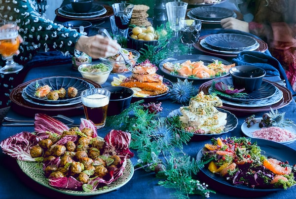 Table covered with a blue tablecloth and plates with meatballs, veggieballs, salmon