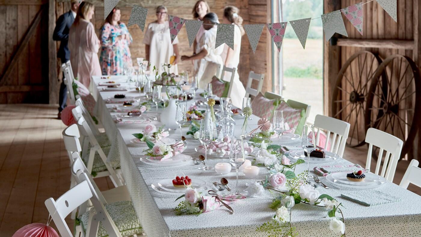 Table de fête dressée dans une grange avec verres, vaisselle et articles décoratifs de la collection festive INBJUDEN.