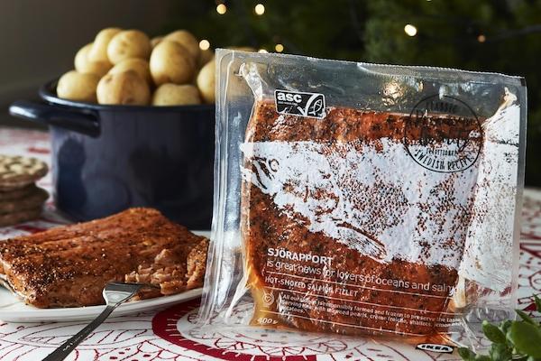 Table de fêtes décorée pour Noël avec une assiette de saumon au poivre et une casserole de pommes de terre