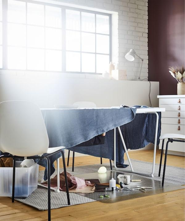 Table de salon avec une longueur de tissu tombant sur les côtés, encadrant un atelier improvisé pour dessiner ou autre activité.