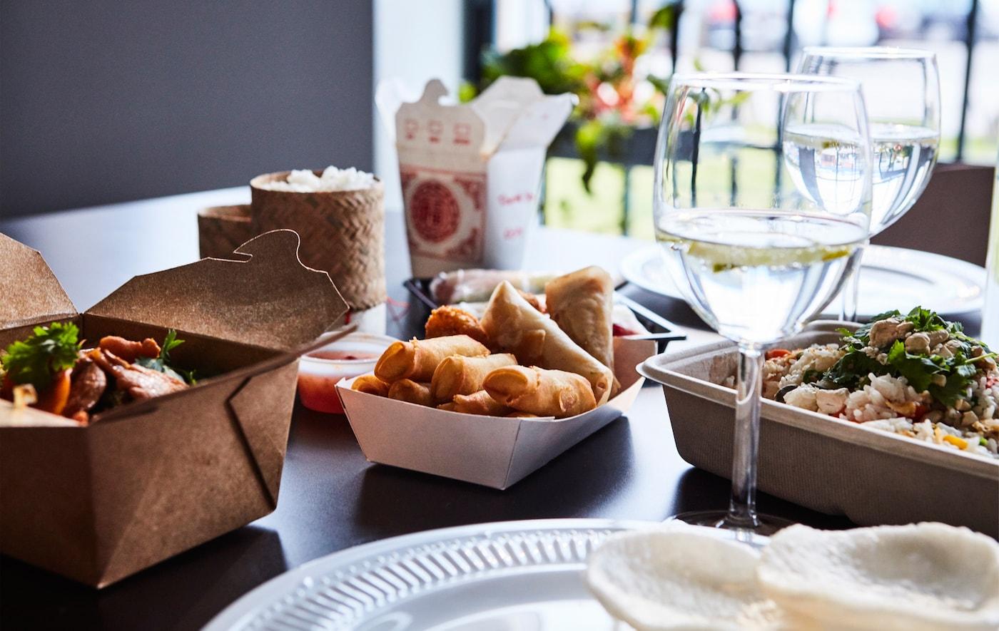 Table dressée avec verres à vin, vaisselle et plats à emporter asiatiques.
