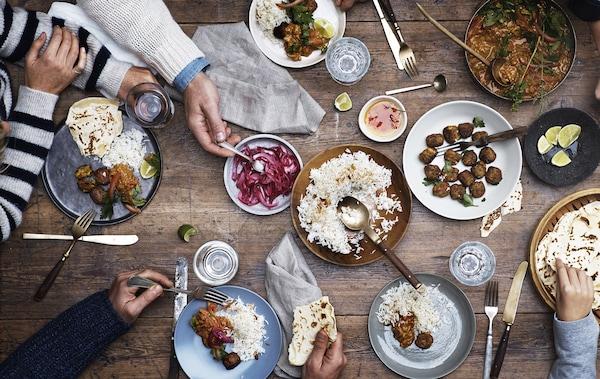 Table en bois sur laquelle sont présentés des boulettes, du riz et des légumes en saumure, avec couverts et mains qui se servent.
