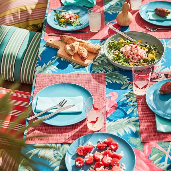 Table extérieure avec des verres SOMMARLIV et des assiettes FÄRGRIK colorés.