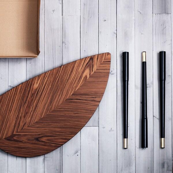 Table LÖVBACKEN signée IKEA, démontée en quatre parties, posée sur un sol en bois blanc.