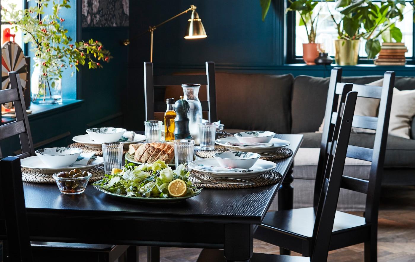 Table noire extensible, dressée pour un déjeuner léger, entourée de chaises de salle à manger.