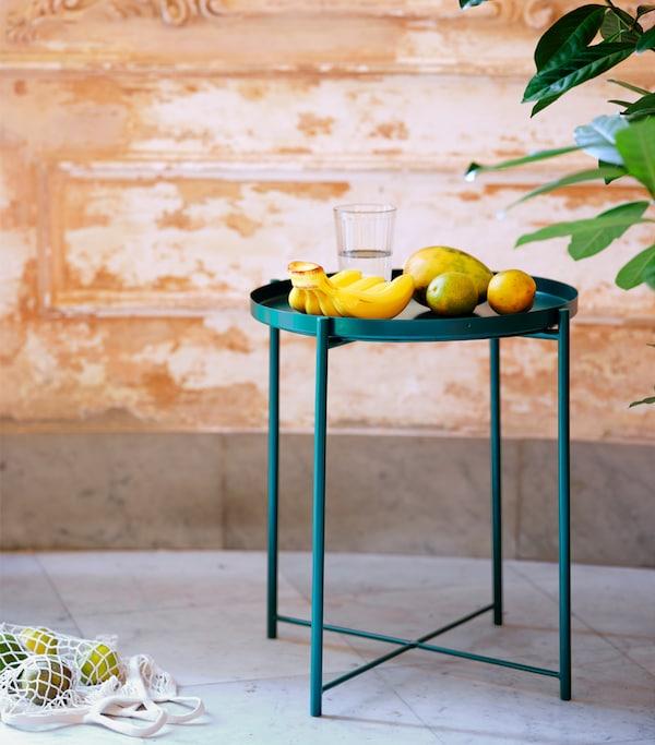 Table/plateau vert foncé sur une surface carrelée. Des bananes et différents agrumes sont posés sur le plateau.