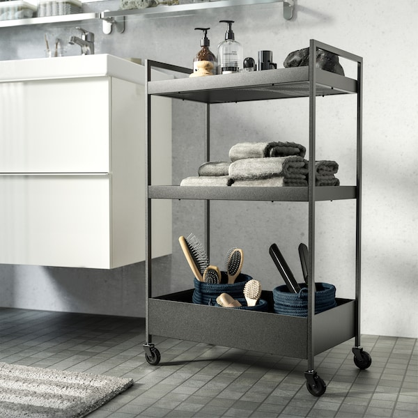 Table roulante noire dans une salle de bain en blanc/gris. Rangée près du lavabo, elle accueille savons, serviettes et brosses à dents.