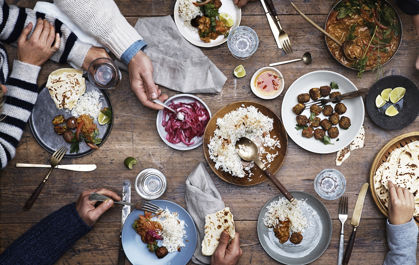 Table setting with meatballs, rice and pickles on a wooden table with cutlery and hands serving.