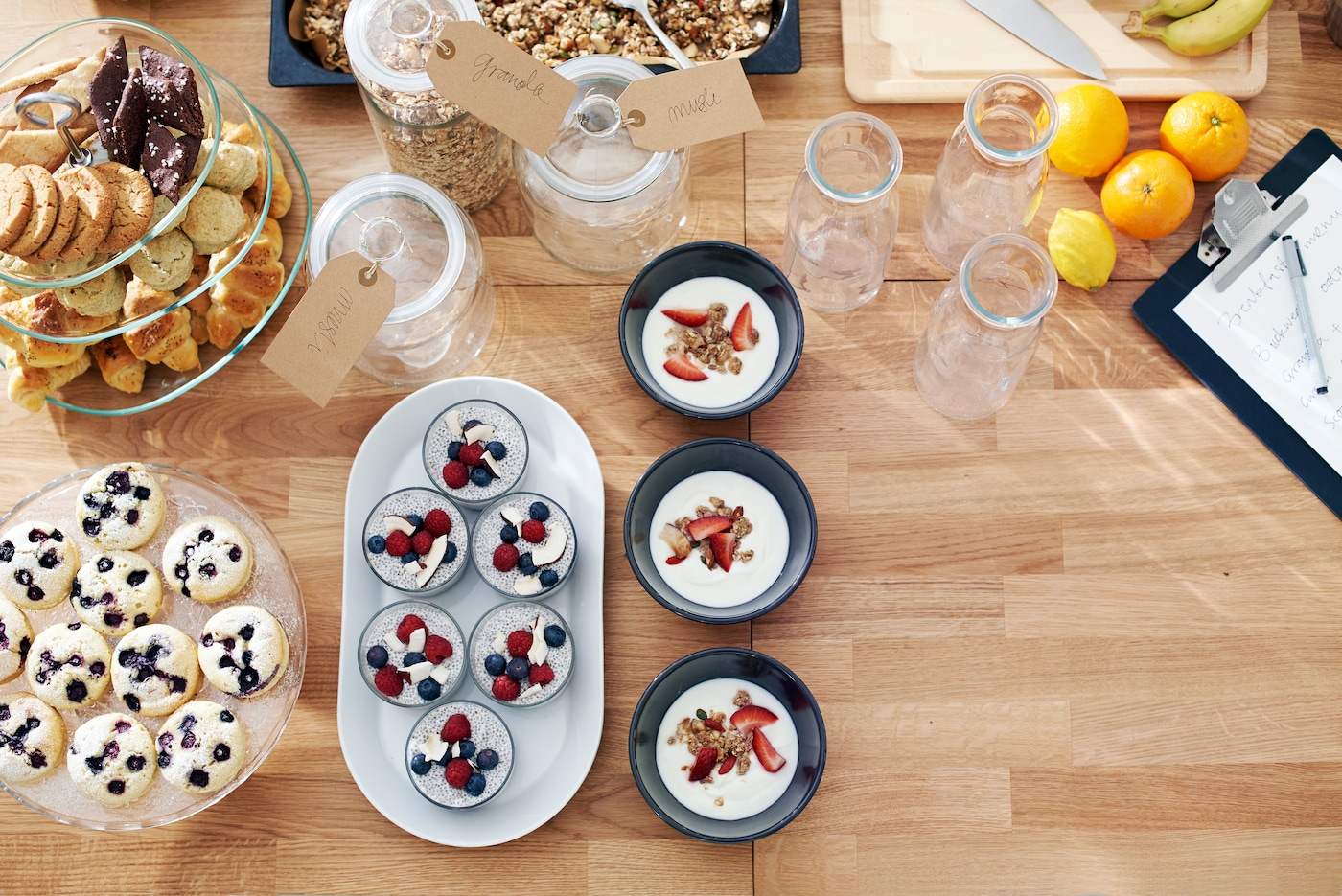 Table with biscuits, granola, fruit and other desserts.