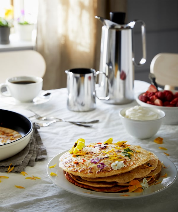 Table with cloth set for breakfast, with coffee thermos, strawberries with cream and a plate of flower-garnished pancakes.