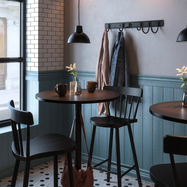 Tables and chairs in a café, vases of flowers and diverse items on the tables, lamps and a coat rack on the wall.