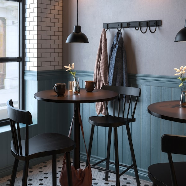 Tables and chairs in a cafe, vases of flowers and diverse items on the tables, lamps and a coat rack on the wall.