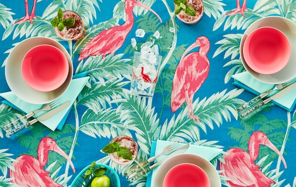 Tabletop with a cloth with a colourful, tropical pattern in pink, green and blue. The table is set with tableware to match.