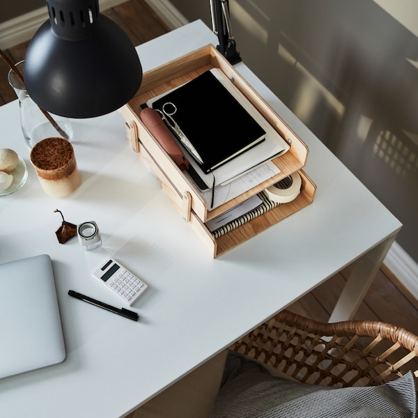 Tabletop with mounted work lamp, laptop and workspace paraphernalia, most of it gathered in a two-layer wooden letter tray.
