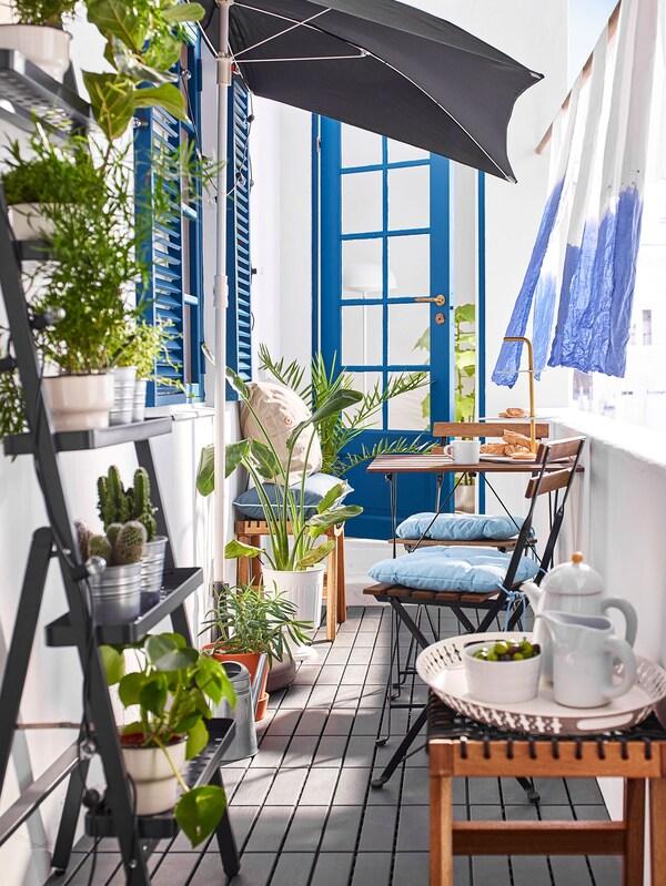 Tabouret d'extérieur brun clair sur lequel sont posés une théière et des raisins, sur un balcon étroit avec chaises et plantes.