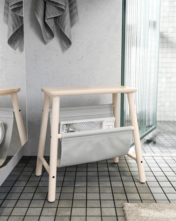 Tabouret en bouleau IKEA VILTO à l'extérieur d'une salle de bain. Des revues sont rangées dans sa poche en tissu gris.