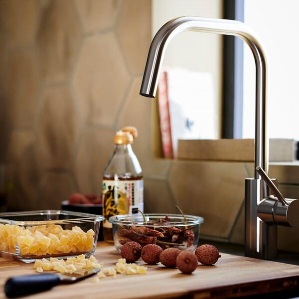 Tábua de cortar em madeira castanha com dois recipientes de vidro, por baixo de uma torneira misturadora de cozinha ÄLMAREN em cor de aço inoxidável.