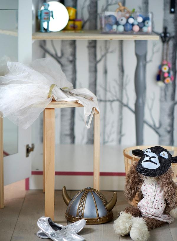 Taburete apilable de contrachapado de abedul FROSTA de IKEA que funciona como mesita para colocar disfraces y muñecos de peluche.