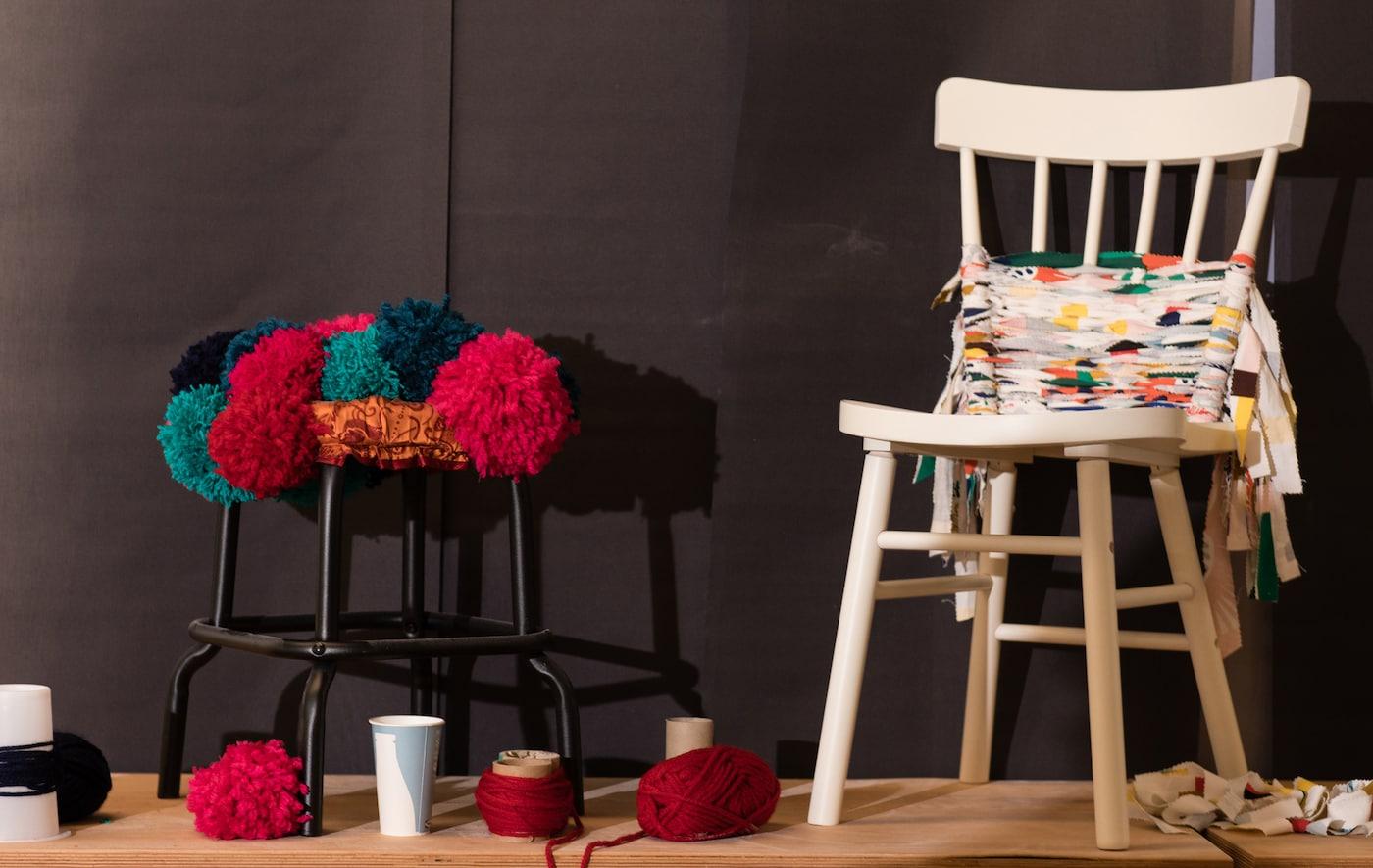 Taburete negro decorado con pompones de lana y una silla blanca decorada con trozos de tela.