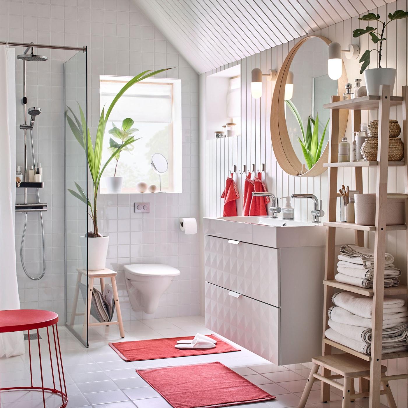 Tämä IKEA-tuotteilla sisustettu valkoinen ja punainen kylpyhuone sisältää valkoisen GODMORGON kahden altaan allaskalusteen, jonka ansiosta monta perheenjäsentä voi peseytyä yhtä aikaa.