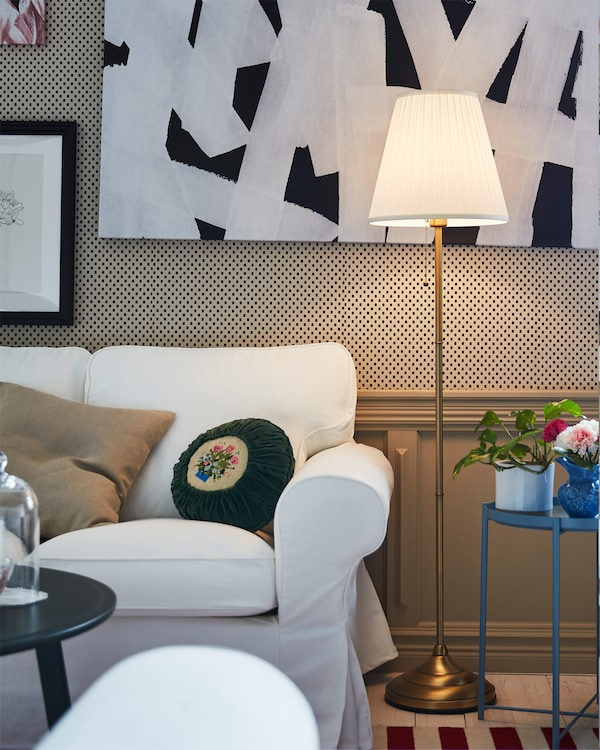 Tänd golvlampa i mässing med vit skärm står intill en vit EKTORP soffa i vardagsrummet.