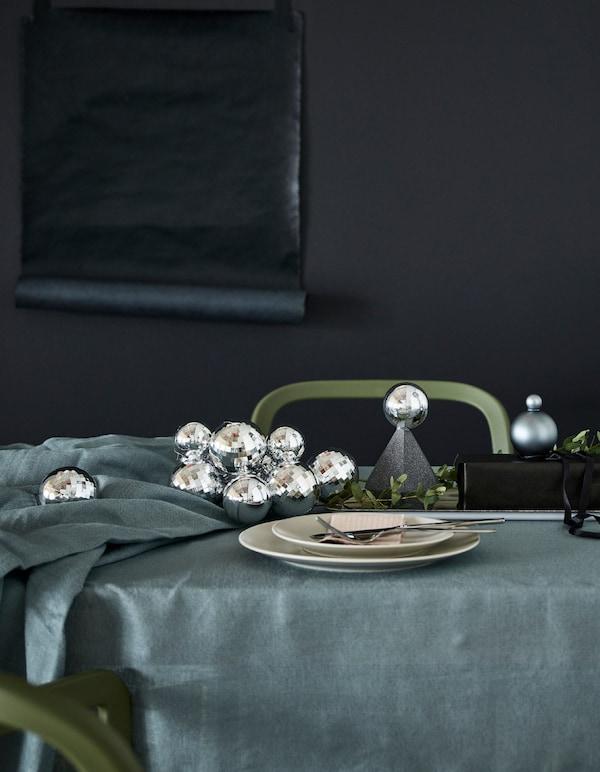 Tafelbedekking met zilverkleurige kerstballen en gerecycleerde geschenkdoosjes.