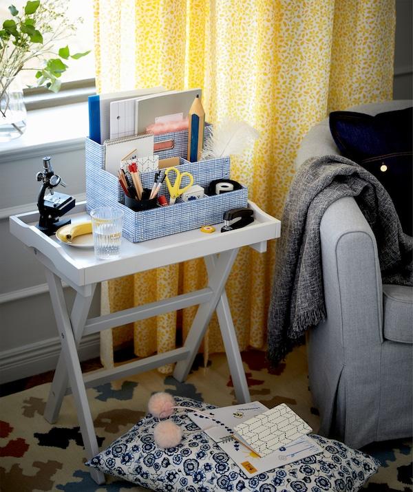 Tálcaasztal fotel és ablak között a nappaliban.
