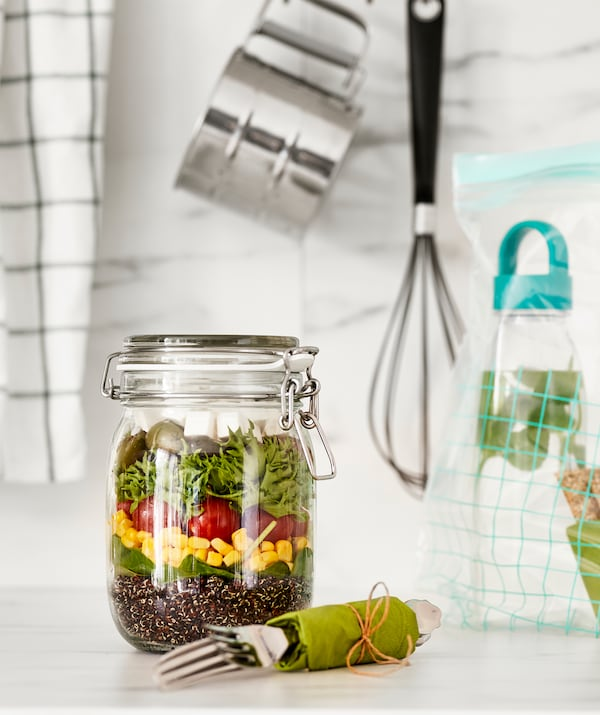 Tall glass jar with fastened lid, holding a layered, Greek-style salad; eating-utensil kit and water bottle on the side.