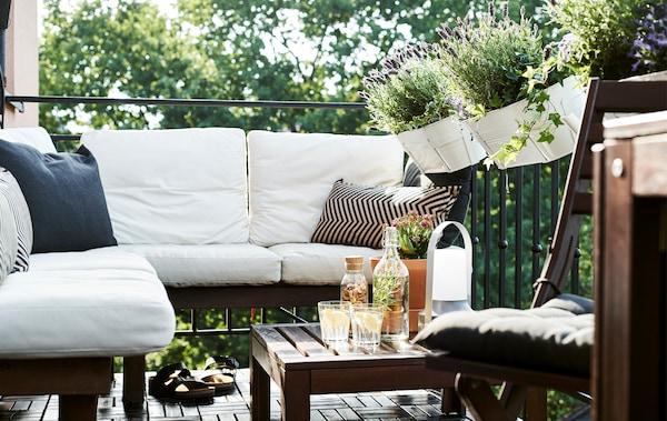 Tamni drveni namještaj s bijelim ukrasnim jastucima na balkonu s teglama za biljke.