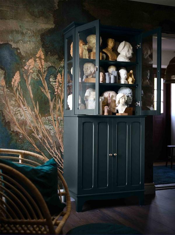 Tamnozelen ormarić sa staklenim vratima je pun staromodnih skulptura.