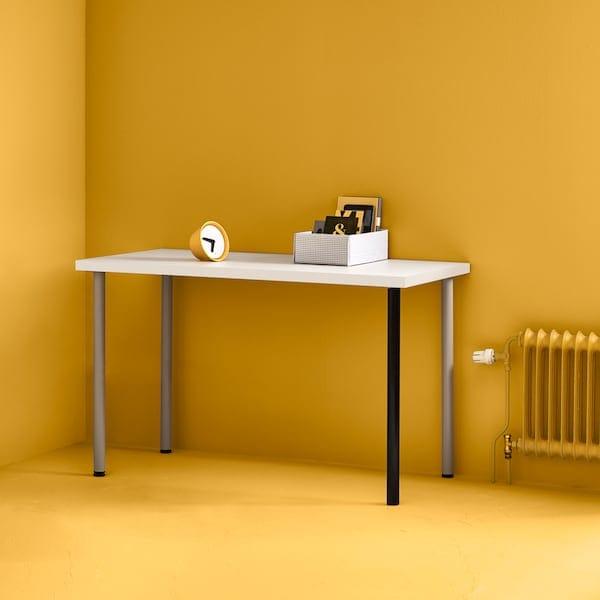 Tampo de mesa LINNMON em branco com pernas em prateado e em preto no canto de uma sala em amarelo vivo com um radiador em amarelo ao lado.
