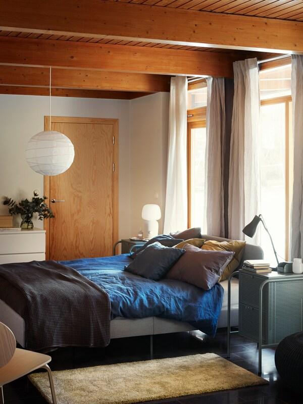 Tapicerowane łóżko SLATTUM z niebieską pościelą ustawione w nasłonecznionej i utrzymanej w jasnej kolorystyce nowoczesnej sypialni.