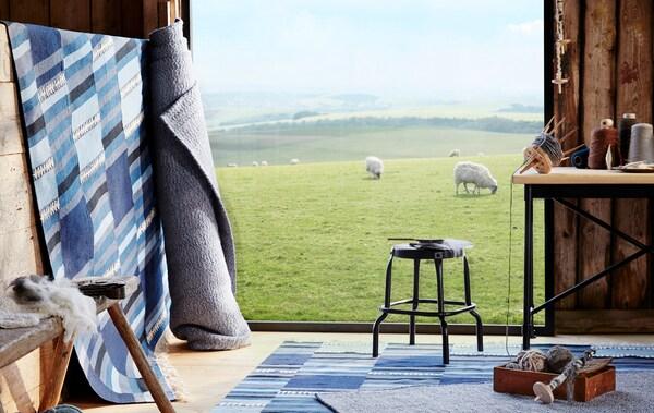 Tapis bleus et gris roulés, mis en valeur dans une grange dont les portes sont ouvertes sur un champ où paissent des moutons.